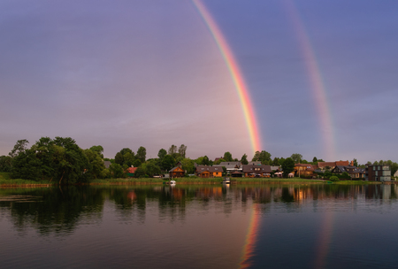Summer landscape with double rainbow and boats.Rainbow over the lake Galve, near of Trakai Island Castle,  Lithuania. View of water landscape with township, green trees and lake under the sky with clouds and rainbow