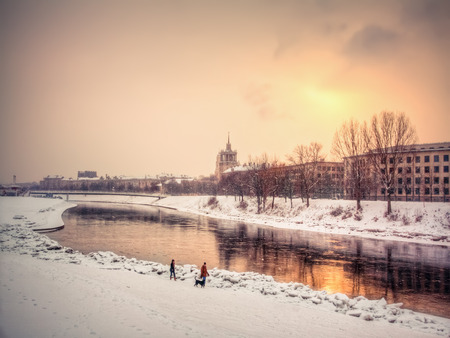 Vilnius / Lithuania. Winter snow Vilnius with views of the river Neris and promenade. Two people (man and woman) and a dog walk along the promenade into the sunset Reklamní fotografie