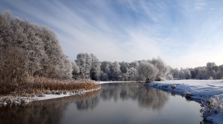 minsk: Winter landscape with frosted river and white snow.Small river in center of Minsk (Belarus), surrounded by snow-covered trees and a beautiful sky with clouds.The bank of the river overgrown with reeds Stock Photo
