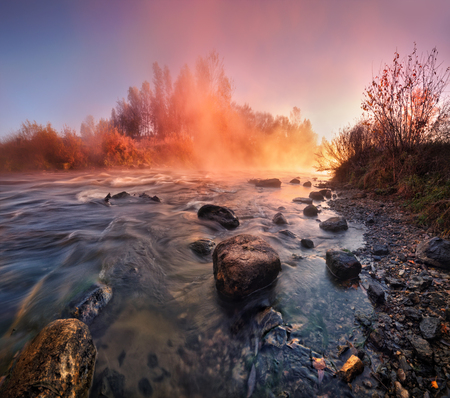 Beautiful autumn foggy morning on the fast river of Belarus in the light of rising sun.Summer misty sunrise on the river. Foggy river in the morning. Summer misty dawn. Foggy morning. Reklamní fotografie
