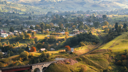 Autumn landscape with a Railway viaduct, mountains and a village located on the slopes of the mountains.Transcarpathia, the border of Western Ukraine and Romania. Autumn pastoral. Rural landscape.