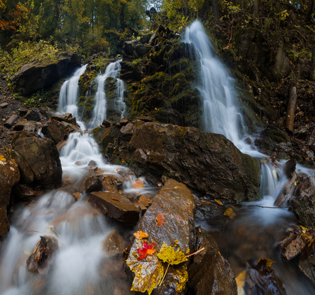 Colorful misty autumn landscape with beautiful waterfall at mountain river in the forest with red and yellow foliage.Trees with leaves.Stones with moss in the water. Blurred water of creek. Nature.