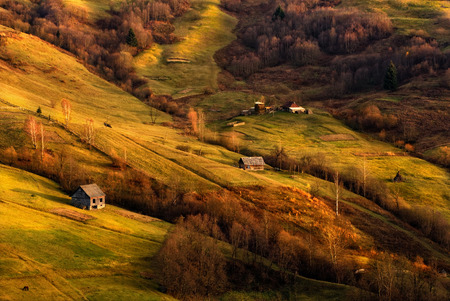 A beautiful autumn rural landscape with lonely houses, beautiful hills and a horse.Autumn evening.The last rays of the sun fall on the slopes.Carpathian rolling landscape on a sunset in autumn colors. Reklamní fotografie