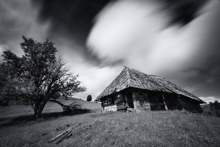 Old spooky abandoned farm house in black-white color. An old, long-abandoned house, against the background of a cloudy sky, shot on a long exposure. Abandoned house in West Ukraine, Carpathian Mountains