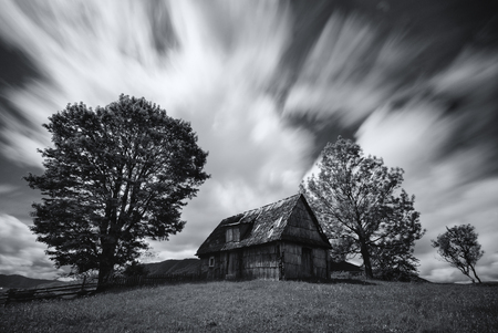 Abandoned house in West Ukraine.Old spooky abandoned farm house in black-white color. An old, long-abandoned house, against the background of a cloudy sky, shot on a long exposure.Carpathian Mountains Reklamní fotografie