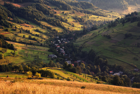 A beautiful summer rural landscape with houses, sunny hills and many small hay stacks. Carpathian rolling landscape on sunset in autumn colors. Picturesque pastoral Ukrainian landscape. West Ukraine