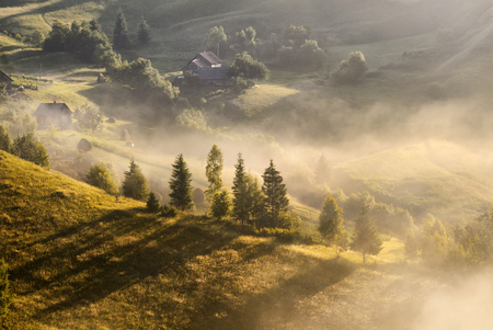 A beautiful autumn foggy landscape with lonely houses and sunny hills. Carpathian rural landscape on sunset in autumn colors. Picturesque pastoral Ukrainian landscape. Foggy morning, West Ukraine