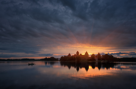 Lithuania, Trakai Castle. Famous Landmark.Fantastically Sunrise Over Medieval Gothic Trakai Island Castle In Lithuania, Located On Galve Lake. Lonely Fisherman In The Boat And Ray Of The Sun Over The Castle Redakční