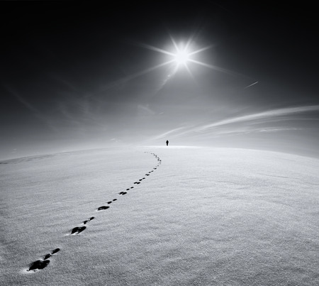 Earth. Universe.Lonely man walking on a snow crust field on the trail of a hare on the background of the sun and the flying plane. Abstract photo silhouette of a man on the road in winter. Reklamní fotografie