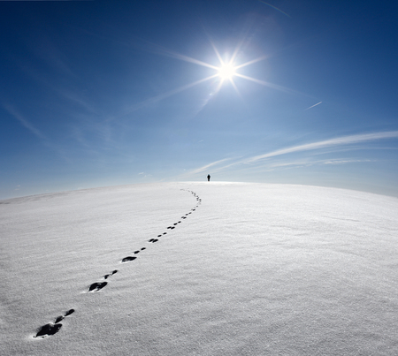 Man, Earth, Universe. Lonely Man Walking On Snow Crust On The Background Of The Sun And Flying Plane. Abstract Photo Silhouette Of A Man On The Road In Winter Empty Field Reklamní fotografie