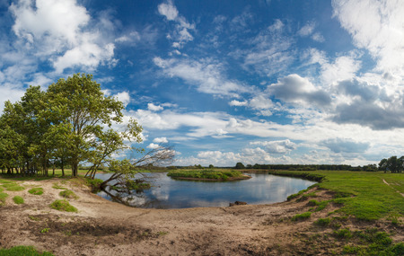 A beautiful panoramic summer landscape with a fisherman, river and a beautiful cloudy sky.The riverbank, covered with green young grass and a lone fisherman.The end of spring, the beginning of summer