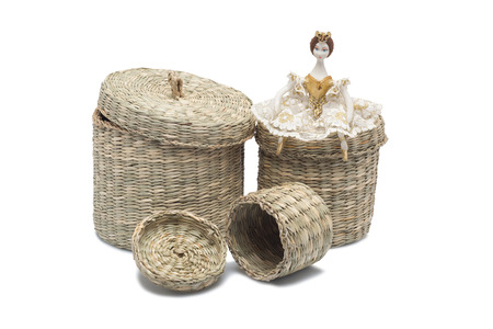 basket embroidery: The doll of a little girl sitting on wicker baskets Stock Photo