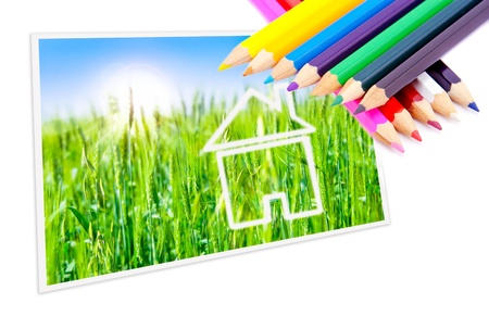 Drawn dream house on a background of green fields and sunny sky, colored pencils. photo