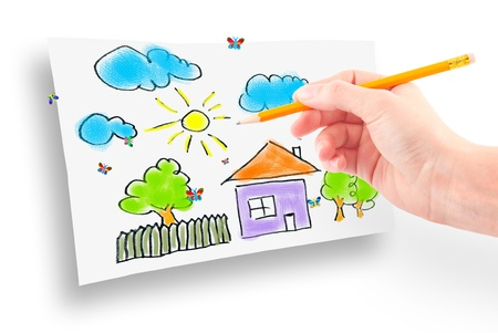 Womans hand with the pencil and brushes drawing the dream home on a white sheet of paper photo
