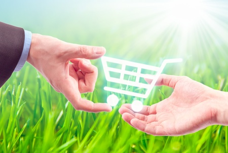 Hand gives a shopping cart on the nature background Stock Photo - 9698705