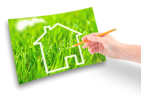 Hand of a girl with a pencil draws a house against on the green grass. photo