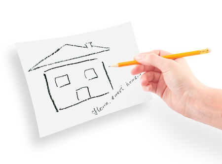 womans hand with the pencil drawing the dream home on a white sheet of paper. photo