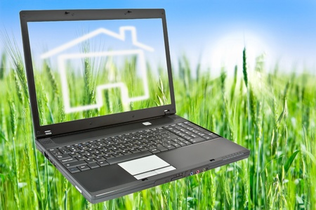 Laptop on green grass with home of dream on a sunny day. photo