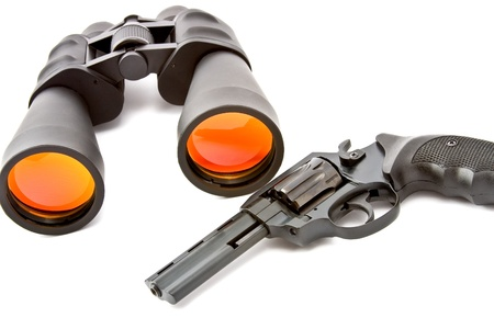 far away look: binoculars and a revolver on a white background Stock Photo