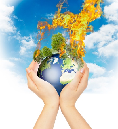 end of the day: Womanish hands holding burning Earth as a symbol of global warming or an apocalypse. Stock Photo