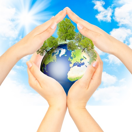 Hands and Earth on sky background. Earth our home concept photo