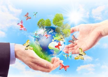 La terra in mani umane, erba, alberi e farfalle. Concetto di terra del patrimonio per le generazioni future Archivio Fotografico - 9698531