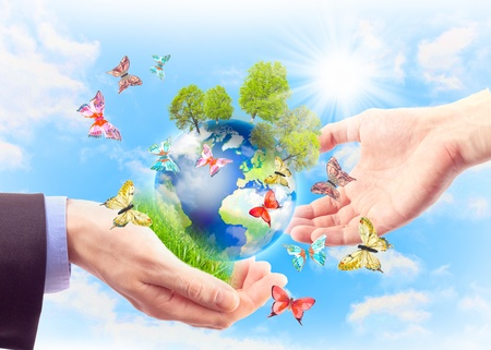 and harmony: The earth in human hands, grass, trees and butterflies. Concept of heritage earth for future generations Stock Photo