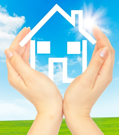 Hands holding model of a house on nature background photo
