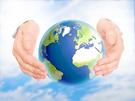 Earth in human hand against blue sky. Environmental protection concept. photo