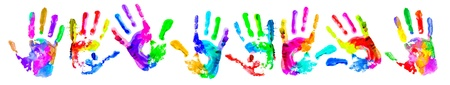 ethnic diversity: Multi coloured painted handprints arranged in a circle on a white background. Stock Photo