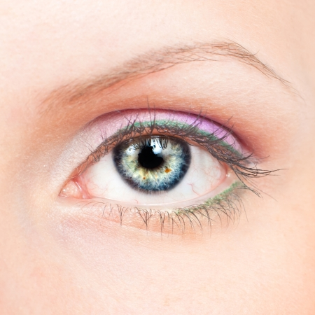 Close-up of beauty female eye with pink and green make-up photo