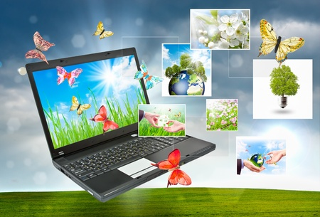 Colorful collage of laptop against green nature background photo