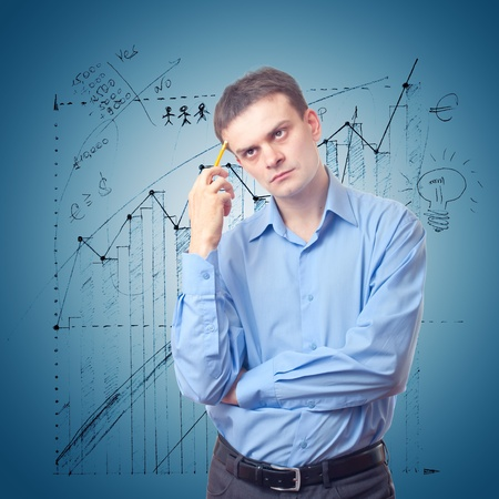 Young businessman in thinking on the background of the chart Stock Photo