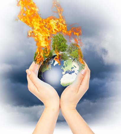 Womanish hands holding burning Earth as a symbol of global warming or an apocalypse. photo