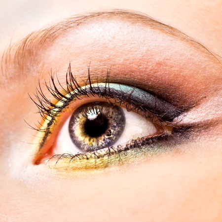 Close-up of beautiful womanish eye with yellow and green make-up photo