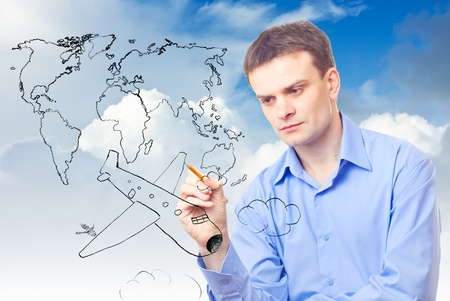 Businessman drawing plane and world map on a sky background photo