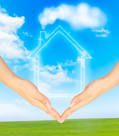 secure home: Hands holding model of a house on nature background Stock Photo