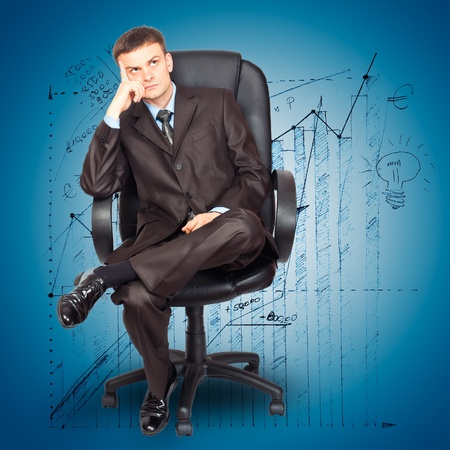 Portrait of young businessman sitting on chair against graph background photo