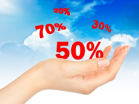 Flying Sale numbers on hand on blue sky background photo