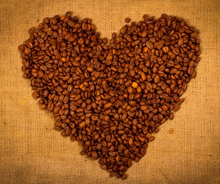 Heart shape created with coffee beans on a sacking background photo