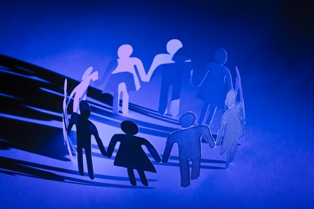 Group of paper doll people holding hands. Social network concept photo