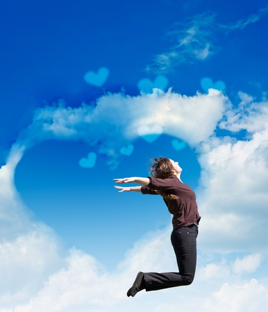 Girl jump on the background of the cloudy sky. Heart made from cloud in the blue sky photo
