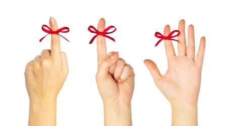Red bow on finger isolated on white background Standard-Bild