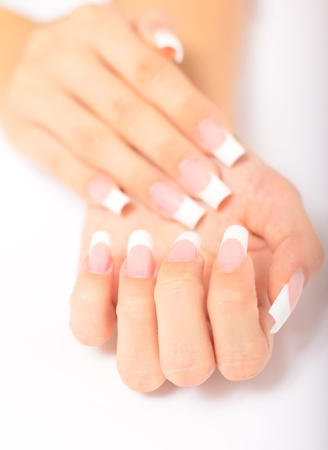 Beautiful female hands with french manicure on a light background with a shadow photo