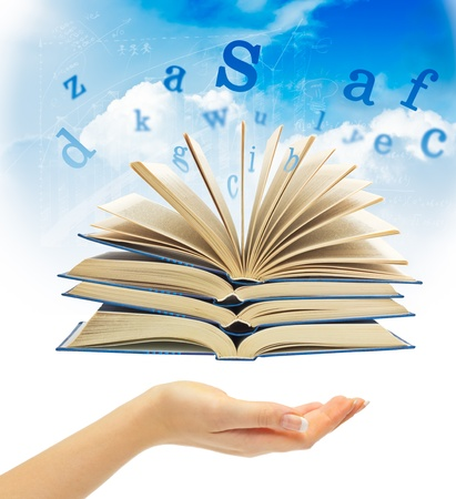 The Magic Book and the letters over hand on a sky background. Education concept photo