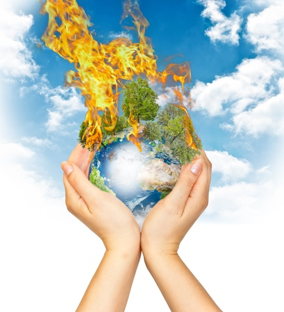 Womanish hands holding burning Earth as a symbol of global warming or an apocalypse photo