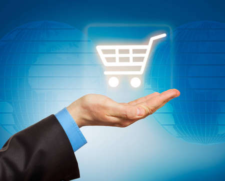 Man hand holding shopping cart icon. Conceptual image photo