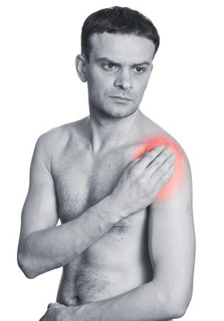 hombros: El hombre joven que sostiene el hombro con dolor. Aislado en blanco