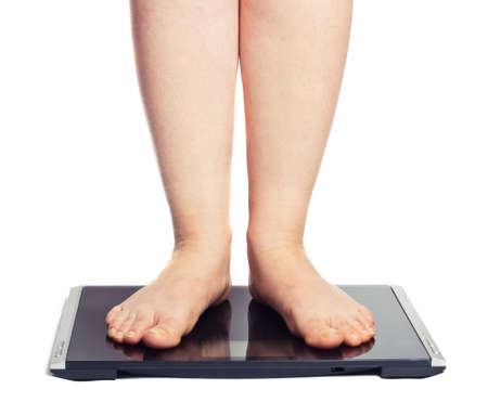 bathroom scale: Bare female feet standing on bathroom scale. Isolated on white Stock Photo