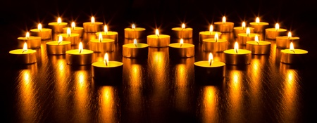 Panorama of the many burning candles with shallow depth of field